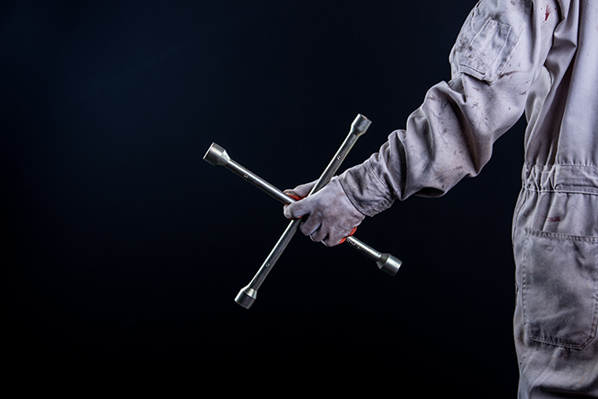 Car mechanic wearing a white uniform stand holding wrench isolated on gray background with copy space.